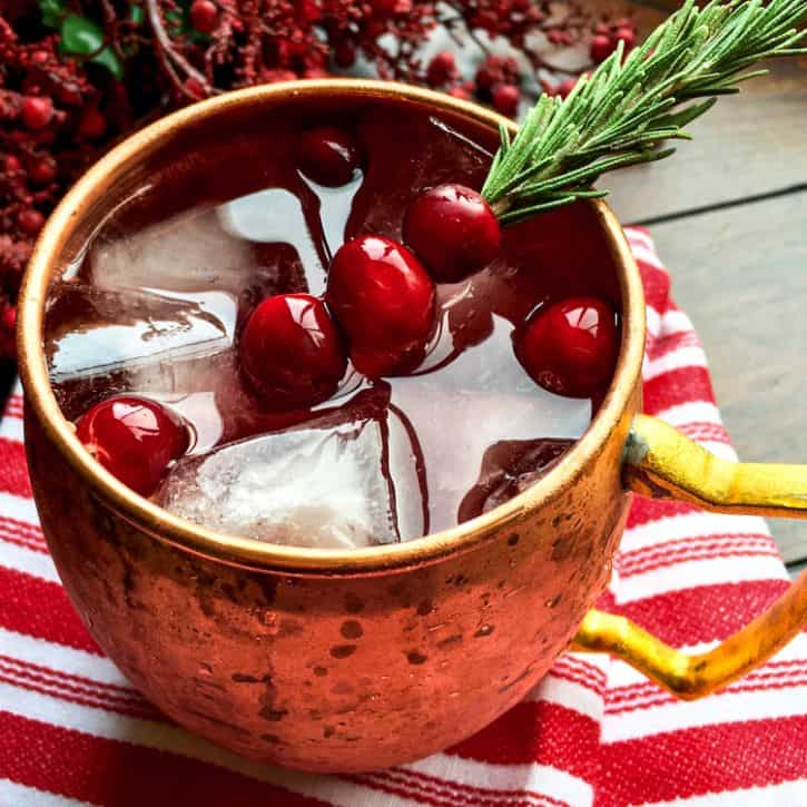 cranberry mule in a copper cup garnished with fresh cranberries on a rosemary sprig